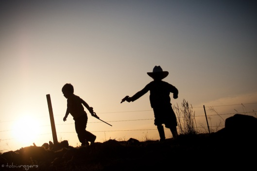 Silhouette of two young boys playing cowboys with a cap gun and rubberband gun.